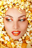 Woman beauty face with unhealth eating fast food popcorn potato Stock Photography