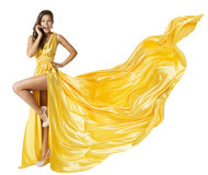 Woman Beauty Fashion Dress, Beautiful Girl In Flying Yellow Fluttering Gown, Standing on One Leg High Heels, Fabric Cloth Waving royalty free stock photo