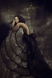 Woman beauty fashion dress, girl in draped gown ov. Er artistic grunge dark background Stock Photo