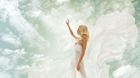 Woman beauty, girl in fluttering dress over sky Royalty Free Stock Images