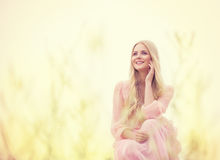Woman Beauty Outdoor Portrait, Beautiful Fashion Model. In Pink Dress over yellow field background stock image