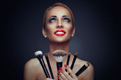 Woman beauty portrait with brushes on a dark background Stock Image
