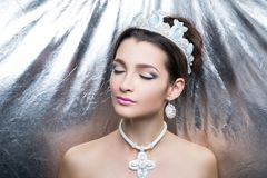 Woman white queen. Woman beauty queen close up portrait model. Massive jewellery made of beads, crystals earrings cross-stitch big cross. hair-do brunette hair royalty free stock photos