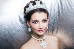 Woman white queen. Woman beauty queen close up portrait model. Massive jewellery made of beads, crystals earrings cross-stitch big cross. hair-do brunette hair stock photos