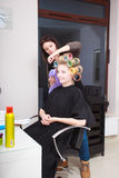 Woman in beauty salon. Blond girl with hair curlers rollers by hairdresser. Hairstyle. Royalty Free Stock Image