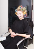 Woman in beauty salon, blond girl hair curlers rollers by hairdresser. Hairstyle. Royalty Free Stock Image