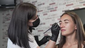 Woman in a beauty salon on eyebrow correction. Browser master paints the client`s eyebrows with a brush stock footage