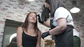 Woman in a beauty salon on eyebrow correction. Browser master treats client with eyebrow scrub stock video footage