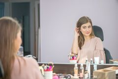 Beautiful woman with hairstyle and makeup looking at the mirror in beauty salon royalty free stock photo