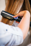 Woman at the beauty salon straightening hair Stock Photo