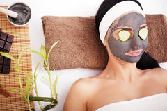 Woman in a beauty salon, wellness. Cosmetic procedure woman`s face in the mask mitigating and cucumber slices on eyes Royalty Free Stock Image