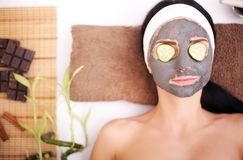 Woman in a beauty salon, wellness. Cosmetic procedure woman`s face in the mask mitigating and cucumber slices on eyes.  Royalty Free Stock Images