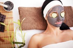 Woman in a beauty salon, wellness. Cosmetic procedure woman`s face in the mask mitigating and cucumber slices on eyes.  Stock Photography