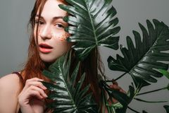 Woman beauty treatment organic cosmetics care. Beauty treatment. Organic cosmetics care. Young pretty woman with monstera. Natural makeup. Glitter freckles stock photo