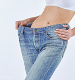 Woman became skinny and wearing old jeans. On white background. concept of healthy lifestyle and beauty Royalty Free Stock Images