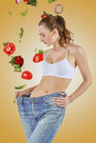 Woman became skinny and wearing old jeans. On white background. concept of healthy lifestyle and beauty royalty free stock image