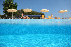Woman becomes tanned near pool under open-skies. In  day-time near deck-chairs and umbrellas, underwater half photo Royalty Free Stock Photos