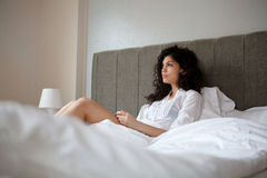 Woman in bed. Thoughtful woman in bed inside her bedroom Royalty Free Stock Photo