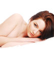 Woman in bed. A young attractive woman lying in a white bed. High key with copy space stock image