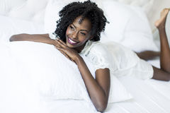 Woman on the bed. African american woman in white on the bed Stock Photos