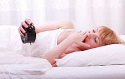 Woman in bed with alarm clock Stock Images