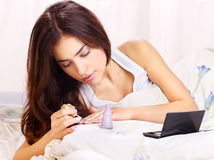 Woman in bed  applying nail polish Royalty Free Stock Photo