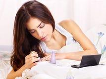 Woman in bed  applying nail polish Royalty Free Stock Photo
