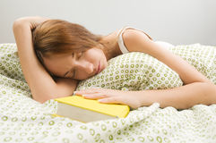 Woman in bed asleep with book Royalty Free Stock Image