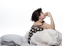 Woman in bed awakening. Young woman in a white sheet bed on white background Royalty Free Stock Photography