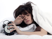 Woman in bed awakening tired holding alarm clock. Young woman woman in bed awakening tired holding alarm clock on white background Stock Images