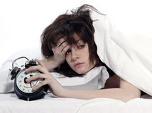 Woman in bed awakening tired holding alarm clock. Young woman woman in bed awakening tired holding alarm clock on white background Stock Photos