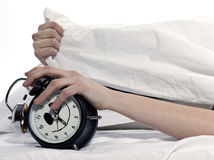 Woman in bed awakening tired holding alarm clock Royalty Free Stock Image