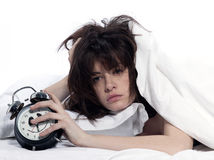 Woman in bed awakening tired holding alarm clock. Young woman woman in bed awakening tired holding alarm clock on white background Stock Image