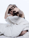 Woman in bed awakening tired insomnia hangover. One young woman in bed awakening tired insomnia hangover  in a white sheet bed on white background Royalty Free Stock Photos