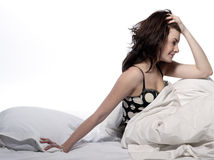 Woman in bed awakening. Young woman in a white sheet bed on white background Stock Photo