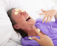 Woman in bed with banana slices on her faces Stock Photography
