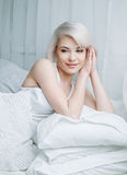 Woman in bed. Beautiful young blond woman relaxing in bed at home Stock Photos