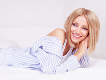 Woman in bed. Beautiful young woman wearing pajamas in bed at home Royalty Free Stock Photo
