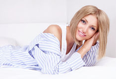 Woman in bed. Beautiful young woman wearing pajamas in bed at home Stock Photography