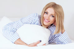 Woman in bed. Beautiful young woman wearing pajamas in bed at home Stock Images