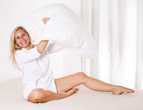 Woman in bed with a big pillow Royalty Free Stock Photos