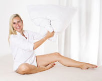 Woman in bed with a big pillow Stock Photography