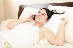 Woman in bed on cellphone Royalty Free Stock Image
