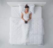Woman in bed connecting with a tablet Royalty Free Stock Photography