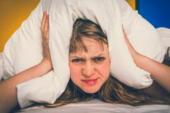 Woman in bed covering ears with pillow because of noise. Attractive woman in bed covering ears with pillow because of noise - insomnia concept - retro style royalty free stock images