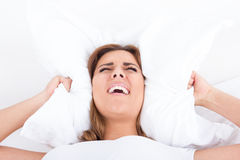 Woman in bed covering ears with pillow because of noise. Young pretty casual screaming woman in bed covering ears with pillow because of noise. Funny image Stock Photos