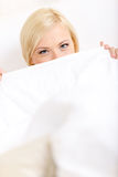 Woman in bed covers her face. With white eiderdown Royalty Free Stock Photography
