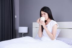 Woman on bed with a cup of coffee in bedroom Royalty Free Stock Image