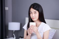 Woman on bed with a cup of coffee in bedroom Stock Image