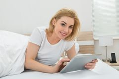 Woman In Bed With Digital Tablet Stock Image